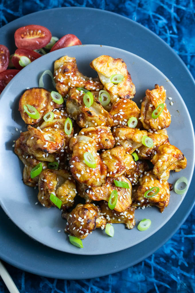 Sticky Sesame Cauliflower | Yup, it's Vegan. Baked battered cauliflower smothered in a sweet and spicy sauce.