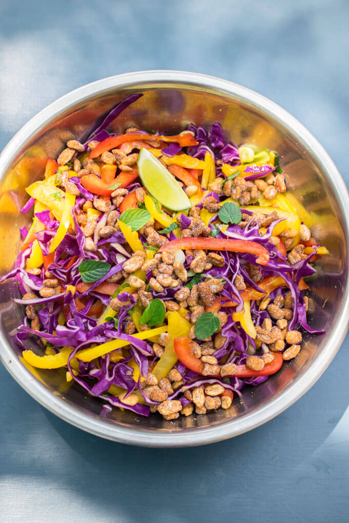 Overhead view of a bowl of Thai cabbage salad with strips of bell pepper and garnished with a lime wedge