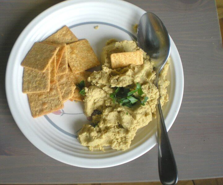 An old photo of a dollop of jalapeño hummus on a plate with some Wheat Thins and a spoon