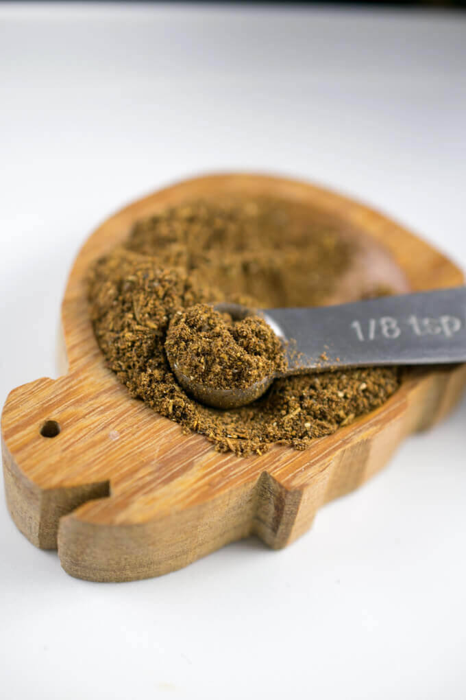 A few spoonfuls of homemade Jamaican jerk seasoning, resting in a wooden dish. Flecks of green and red are visible from the dried thyme and red pepper flakes in the blend.