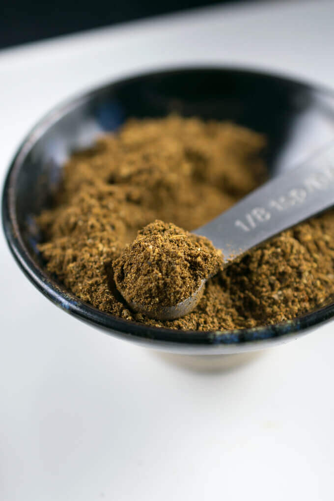 Jamaican jerk seasoning blend being scooped out of a bowl with a measuring spoon