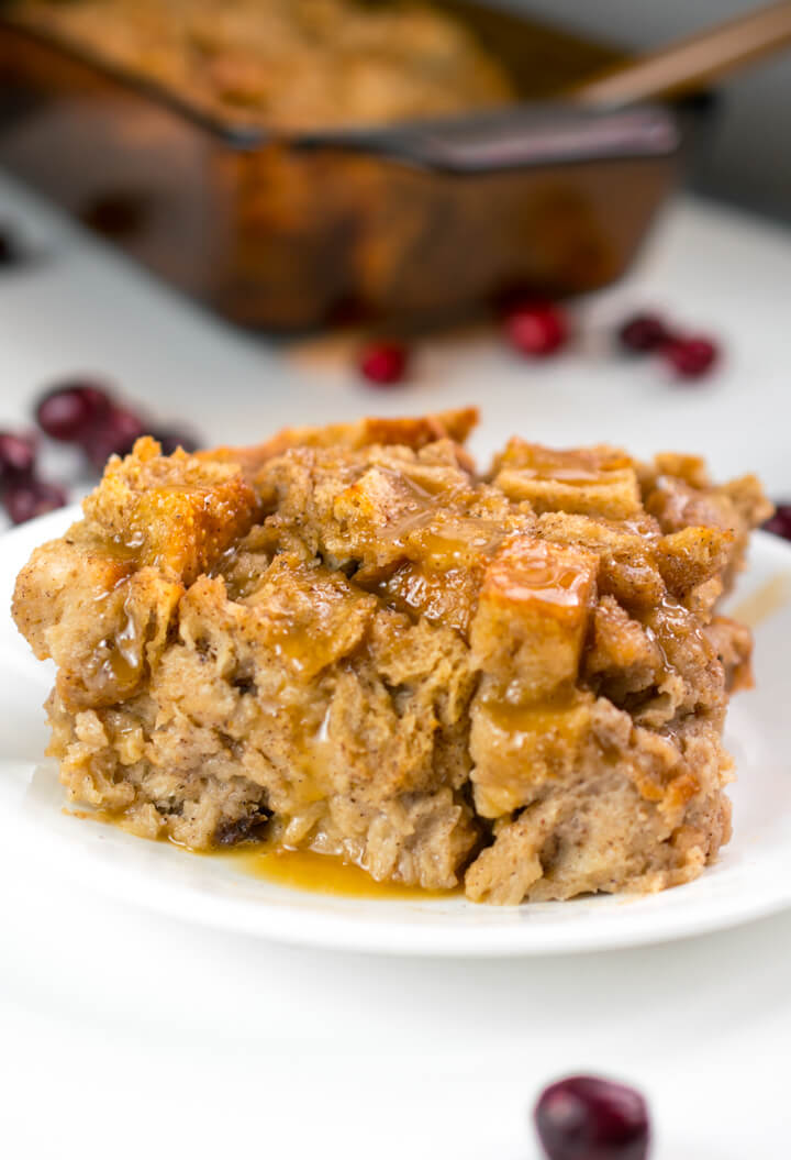 Close-up of a slice of vegan bread pudding with the rest of the dish in the background, showing a moist but well-set texture.