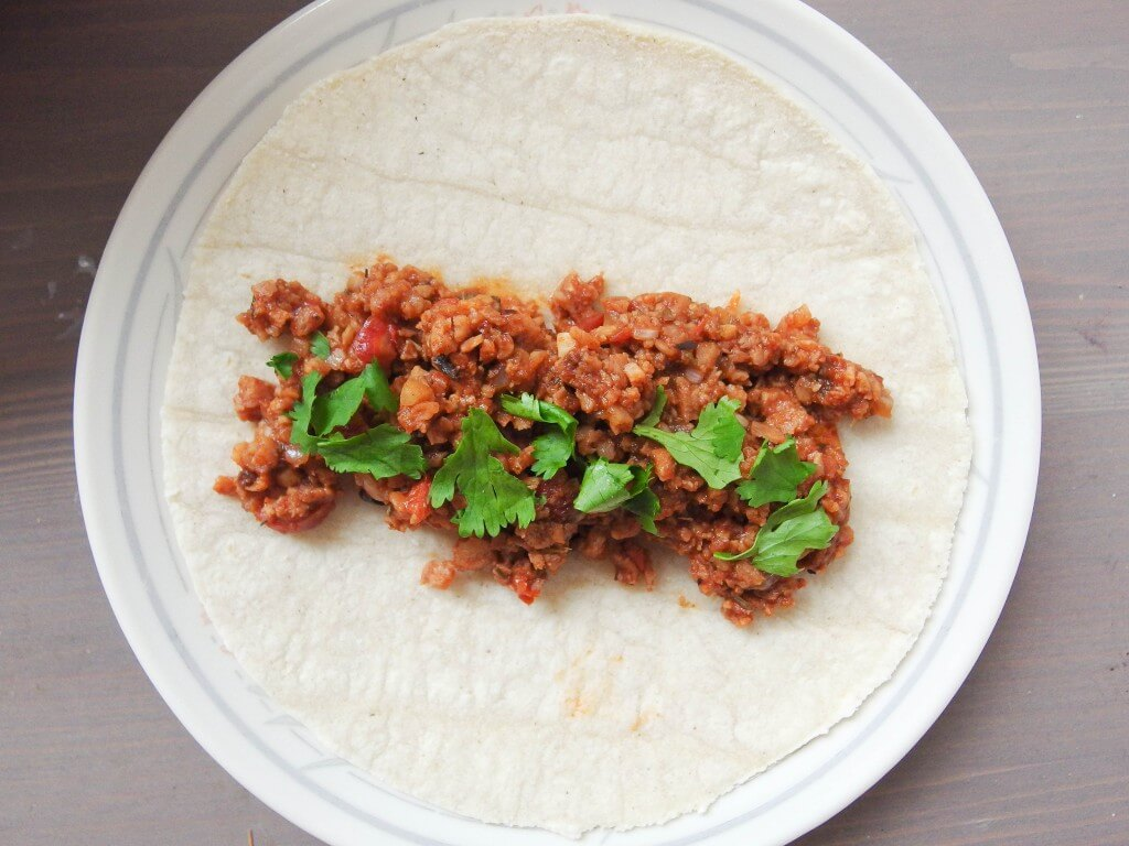 vegan soy chorizo served on small tortilla with cilantro on white plate
