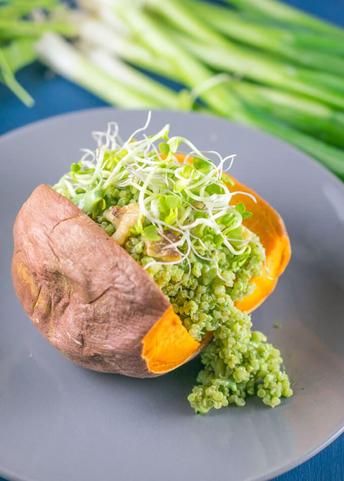 A green goddess quinoa stuffed sweet potato on a plate, topped with a few chopped walnut pieces and daikon radish sprouts. Scallions are in the background.