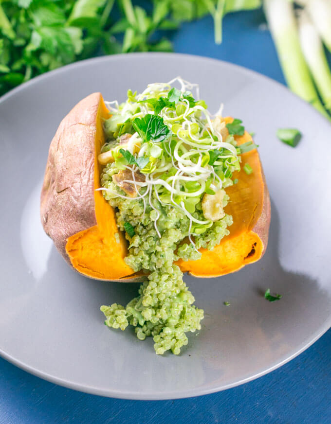 A sweet potato on a gray plate stuffed with green quinoa and topped with bean sprouts and chopped fresh parsley