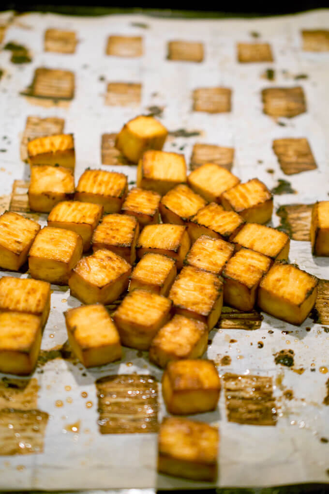 Baked tofu cubes on a baking sheet, ready to be tossed with sweet and sour sauce