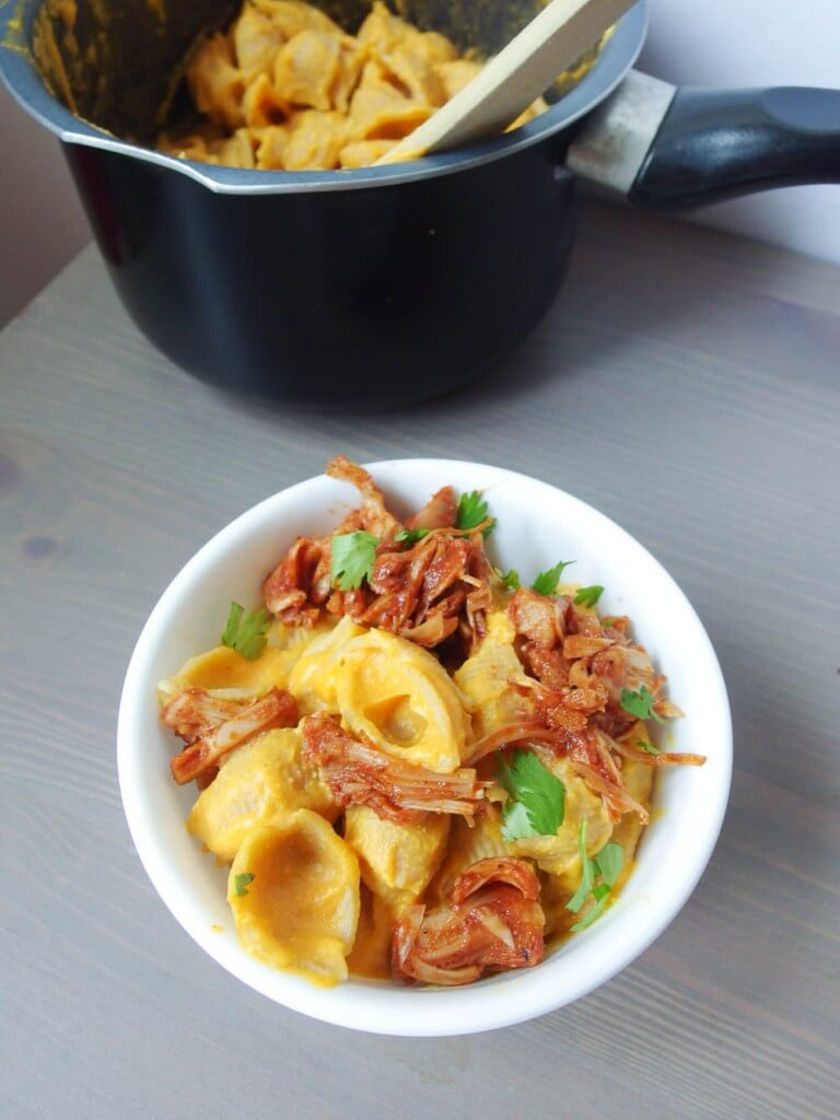 vegan sweet potato cashew mac and cheese with barbecue jackfruit served in a white bowl with a black pot full of