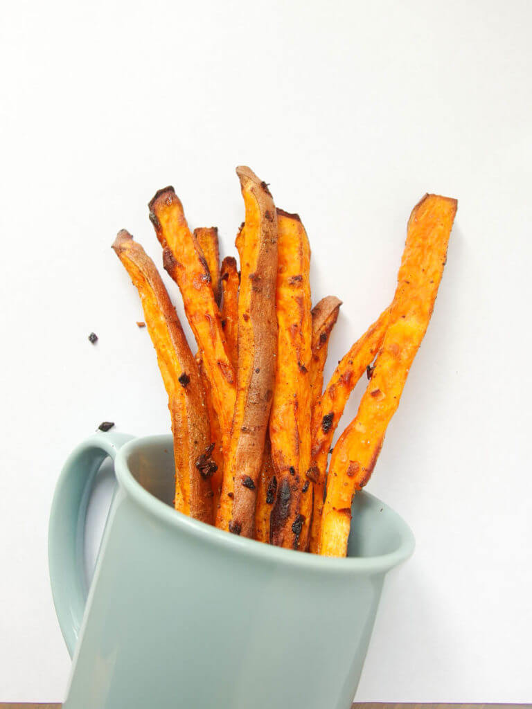 healthy baked sweet potato fries served in a blue mug