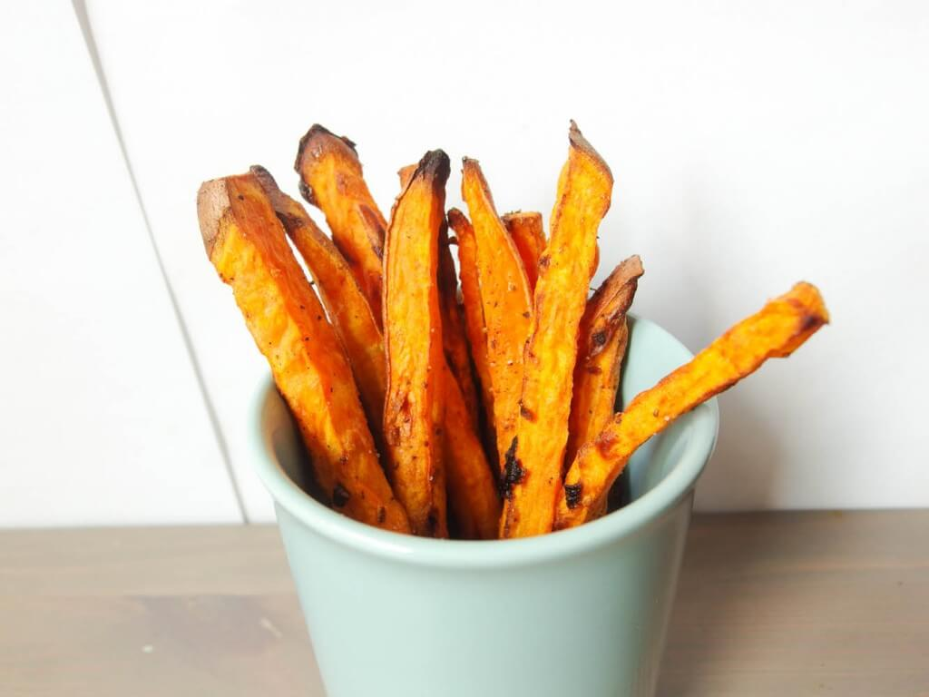 sweet potato fries with garlic and onion served in a blue mug close up