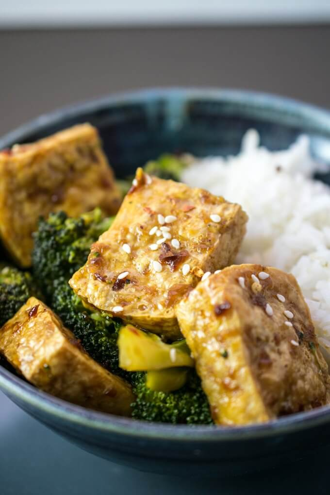 Close-up of tofu bulgogi cubes with a sticky Korean sesame sauce, garnished with sesame seeds and white rice in the background.