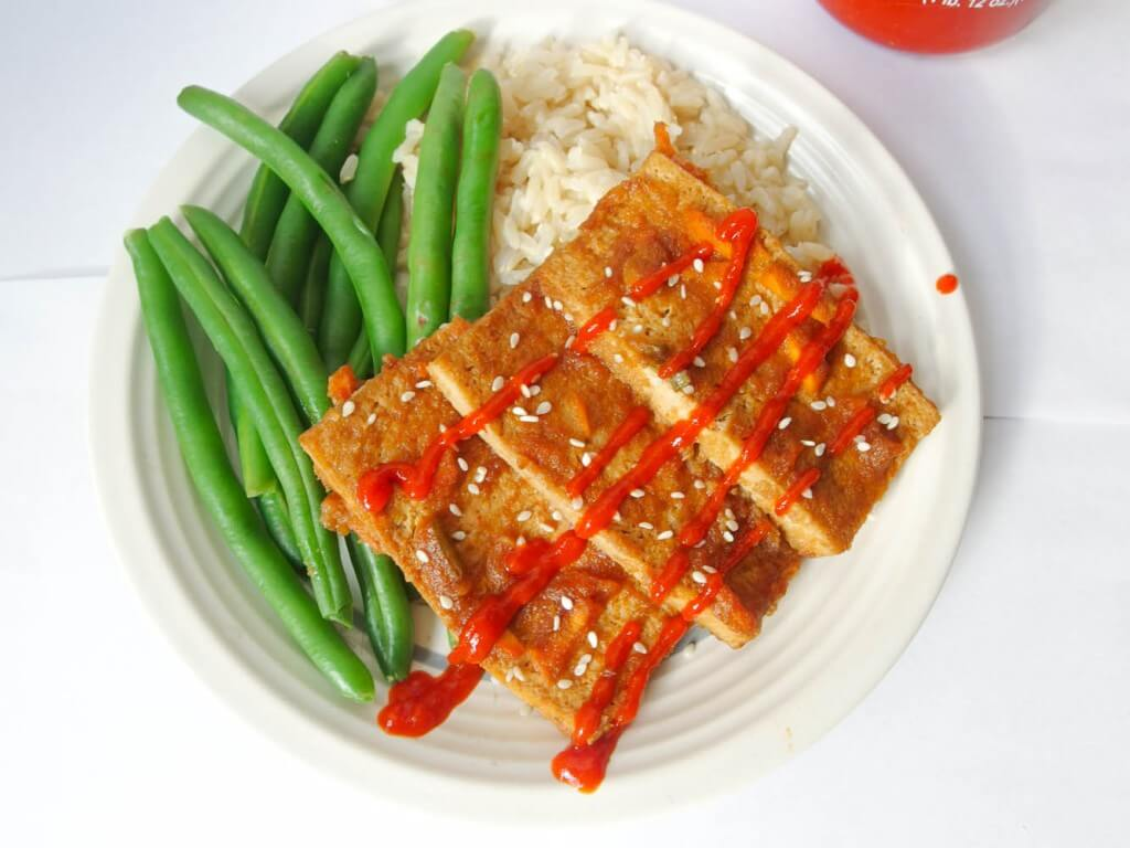 Three slabs of tofu dipped in bulgogi sauce, garnished with sesame seeds and drizzled with sriracha, on a plate next to steamed green beans and brown rice.