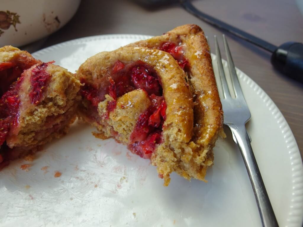 close-up of strawberry breakfast roll with sweet cinnamon icing garnished with flour served with a fork