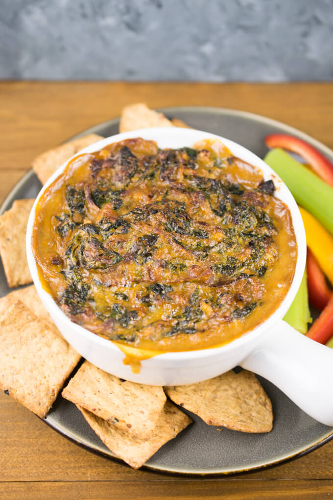 Cheesy vegan caramelized onion and kale dip in a white ramekin served with crackers and veggie strips