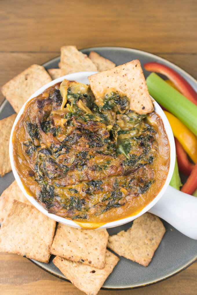 Vegan warm caramelized onion and kale dip after a cracker has been dipped into it - showing the creamy interior.