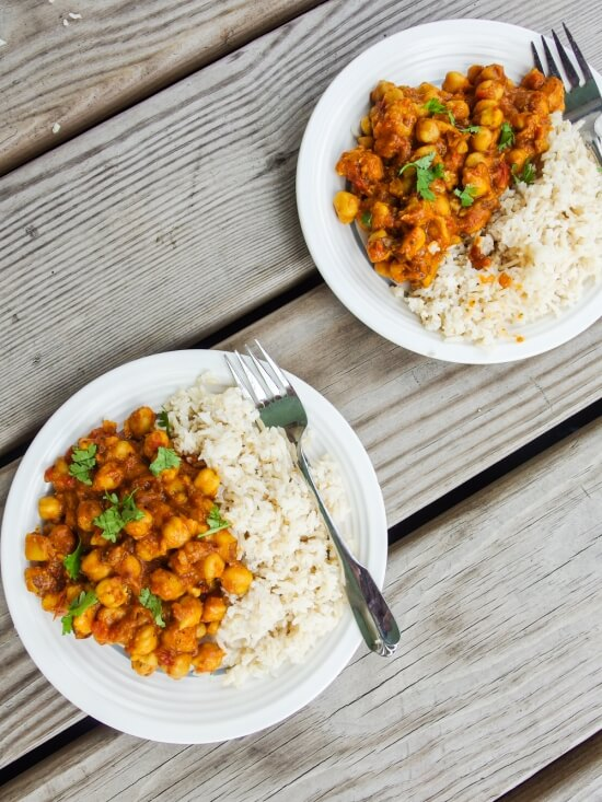 Two fresh plates of chickpea, tomato, and potato vindaloo with fresh cardamom and coriander served over rice with csa vegetables