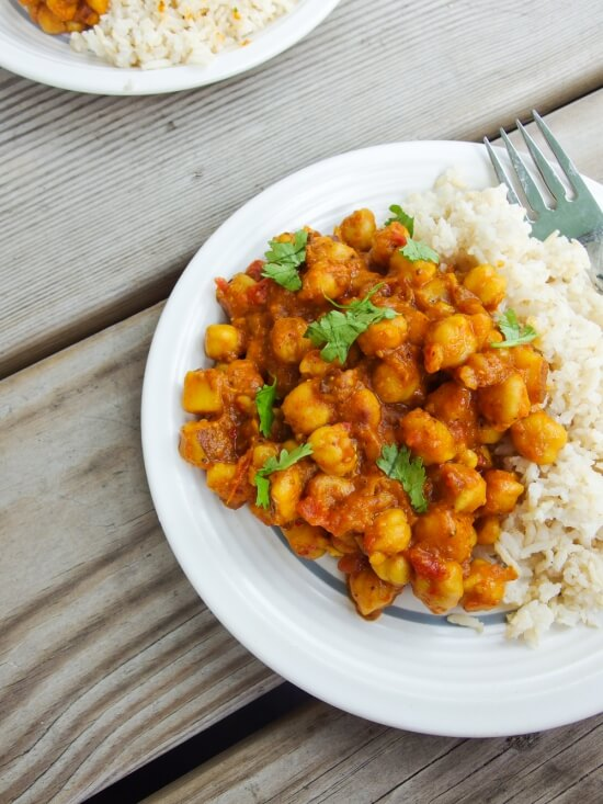 Vegan spicy chickpea curry with fresh ground spices garnished with cilantro served with fluffy rice on a white plate
