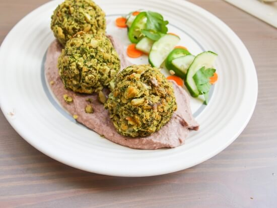 Close up of three vegetable and nutrition packed baked not fried kale falafel served with hummus and jalapeno - a healthy maryland take on a mediterranean classic