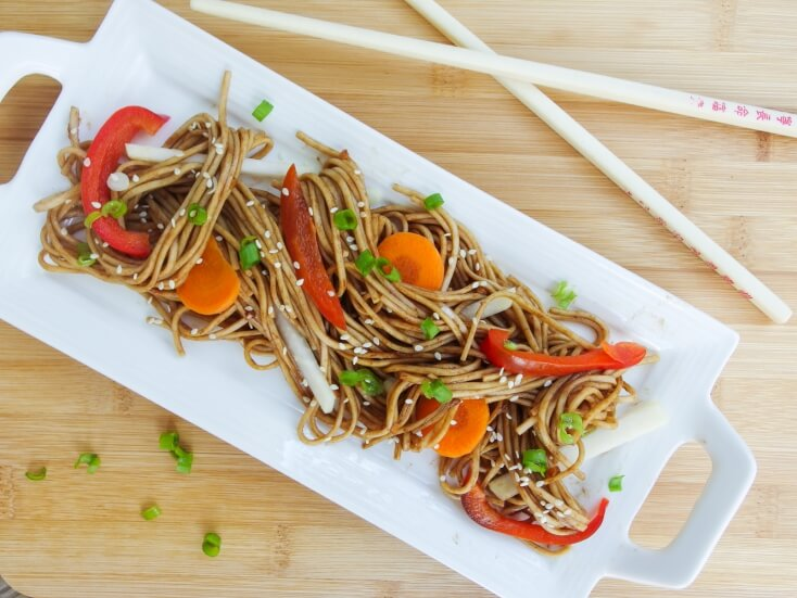 Chilled summer soba noodle salad serve over quick steamed vegetables local and fresh and sesame and crisp green onion with chopsticks - refreshing main dish with gluten free option