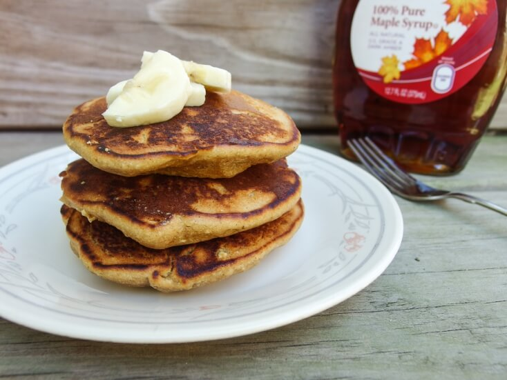 Sweet and nutty coconut sugar, coconut milk, almond, and chickpea pancakes served on a white plate with 100% natural and real maple syrup - light and delicious