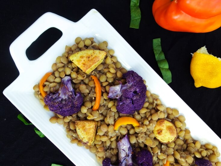 Hearty green or brown lentils served with sweet roasted fall vegetables. Spiced with a homemade ground blend and sweetened with coconut sugar and currants. Served on a white dish with fresh ingredients