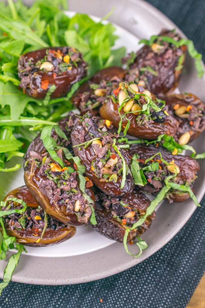 A platter of Medjool dates stuffed with kalamata olive tapenade, with flecks of red pepper flakes and toasted pine nuts.