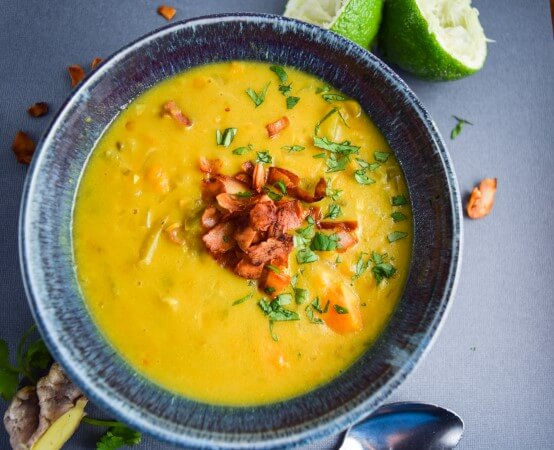 Creamy, nutrient dense sweet potato soup with hearty chickpeas, fresh grated garlic and ginger, spiced curry powder and peppers, and a unique and fragrant coconut bacon make a warming winter meal