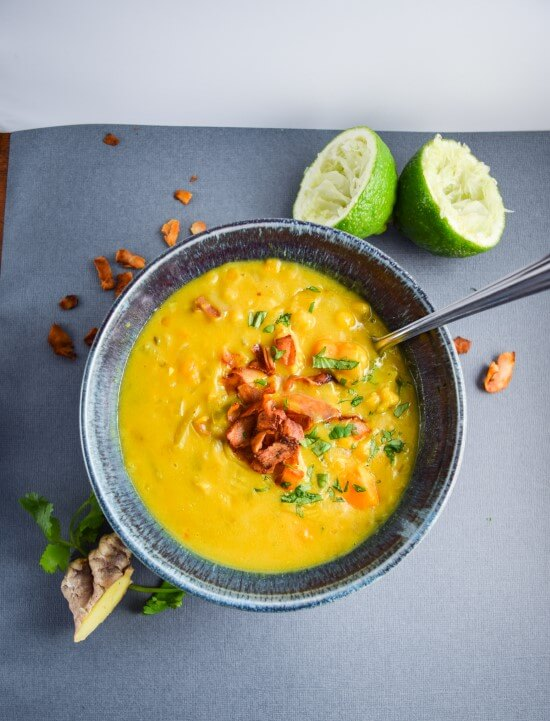 Pineapple juice, maple syrup, and red curry paste make a crispy and smokey coconut bacon. Served on a hot and rich coconut milk and sweet potato chickpea stew with ginger, parsley, and lime juice.