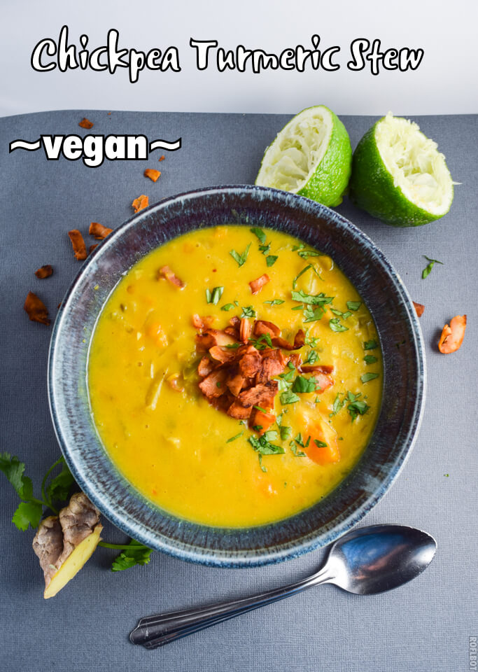 Closeup of a hearty gluten, grain, vegan chickpea turmeric stew garnished with chunky sweet potatoes, red thai curry coconut bacon, lime, and parsley served in a blue bowl