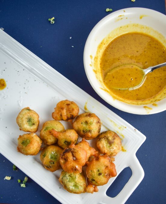 Crispy Brussels sprouts deep-fried to perfection in vegan beer batter served on a white tray with a side of gooey, rich, and spicy maple mustard sauce make a wonderful super bowl addition