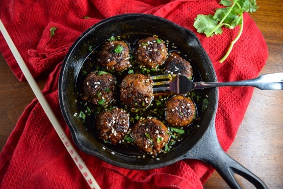One cast iron pan with eight vegan teriyaki meatballs garnished with parsley and sesame seeds make the perfect super bowl appetizer or base for a filling and healthy meal
