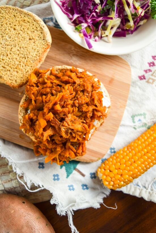 Luscious sweet and spicy bbq pulled sweet potato filling open face on a sprouted grain bun with crunchy vegetable fixings on the side served with corn