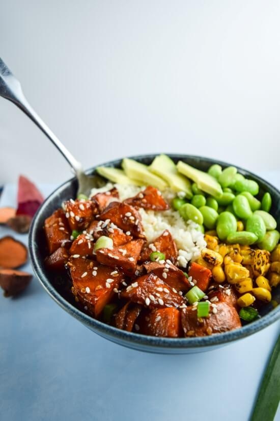 Closeup of a blue bowl of homemade oven roasted teriyaki sweet potatoes, fire roasted corn, fresh edamame, and creamy avocado over cauliflower rice