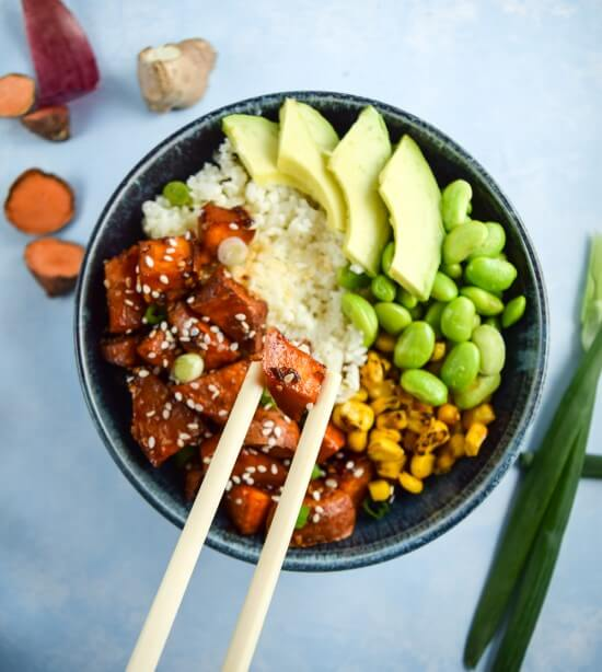 Hearty vegan and gluten free bowls with a riced cauliflower base, bright, nutrient dense green vegetables, and filling teriyaki sweet potatoes topped with scallions and crunchy sesame seeds eaten with chopsticks