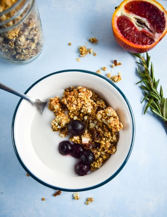 One white bowl of non-dairy milk with oil and refined sugar free vegan granola made with millet and oats and spiced with cardamom, coriander, cinnamon, and ginger. Served with blueberries and grapefruit | yupitsvegan.com