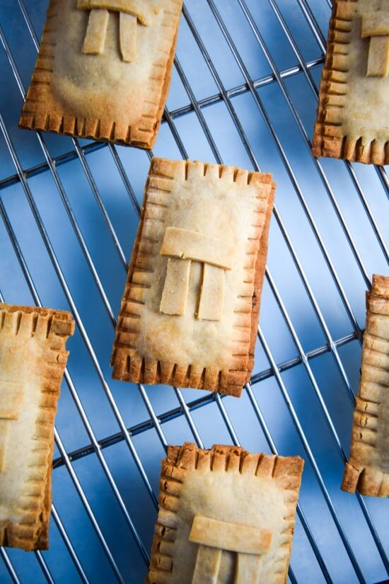 Perfectly crisp and sweet pecan pie poptarts with a perfectly browned decorative crust and a classic sugar glaze shown on a cooling rack - an easy and fast alternative dessert, breakfast, or snack that is sure to impress