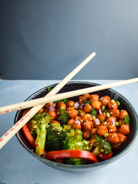 Lightly stir fried chickpeas served with broccoli and red bell pepper strips in a homemade sweet and sticky sauce with a sriracha kick garnished with red onions, green onion, and sesame seeds in a blue bowl with chopsticks