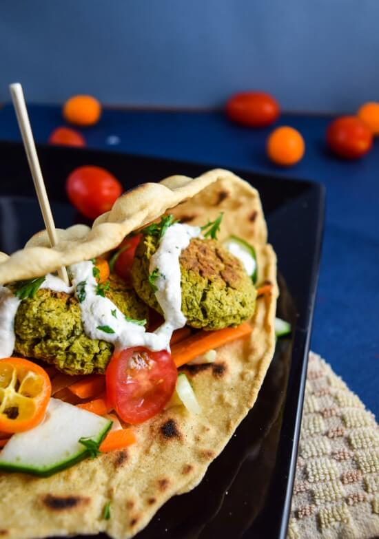 Closeup of crispy baked spinach artichoke falafel with homemade tzatziki sauce, fresh crunchy vegetables, and a tart kumquat addition wrapped in a simple whole grain bread served on a black plate