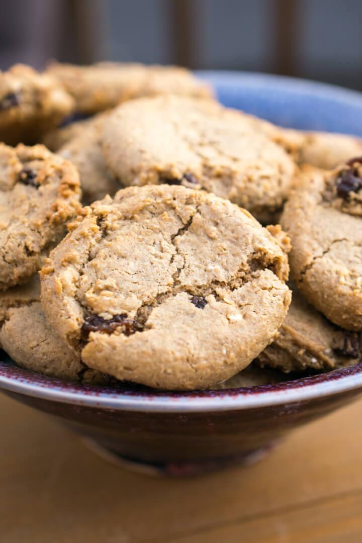 A dozen vegan oatmeal cookies arranged in a ceramic serving bowl.