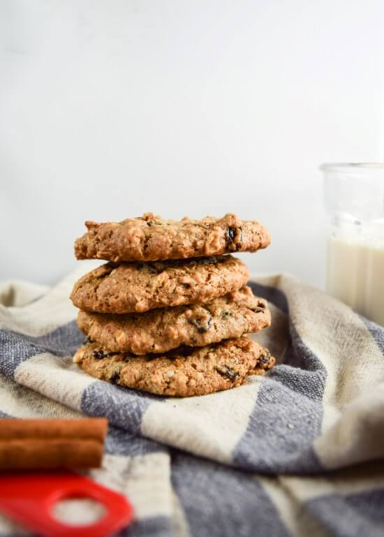 A stack of four vegan oatmeal raisin cookies made with heart-healthy walnuts, hemp seeds, and free of refined sugar on a blue kitchen towel | yupitsvegan.com