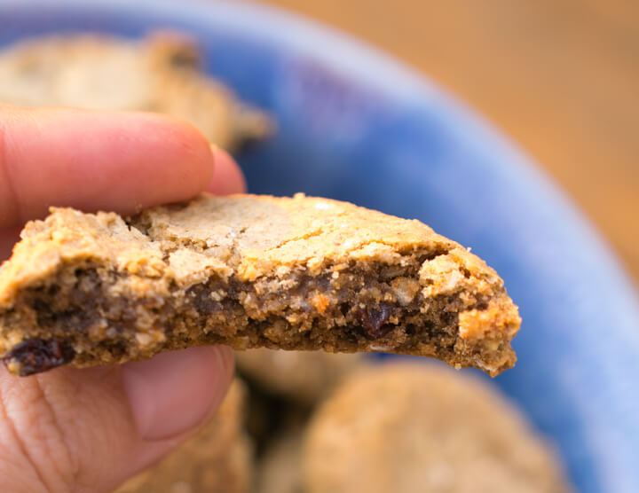 The interior of a vegan oatmeal raisin cookie showing a moist texture with several raisins.