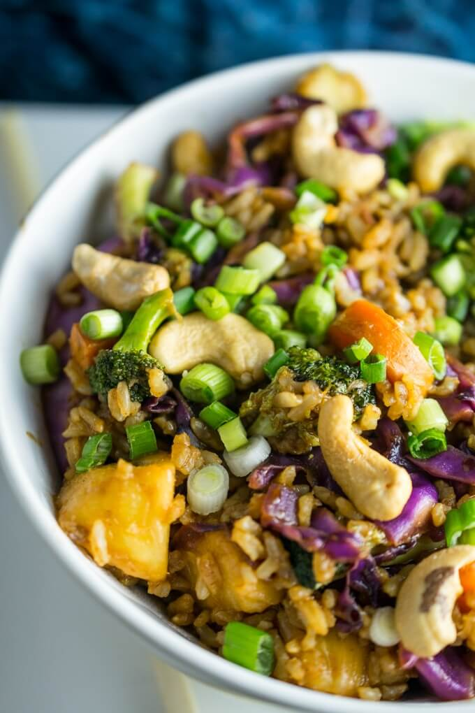 Closeup of fried brown rice with cashew nuts, red cabbage, carrots, broccoli, and tangy pineapple come together in 20 minutes for an easy weeknight dinner
