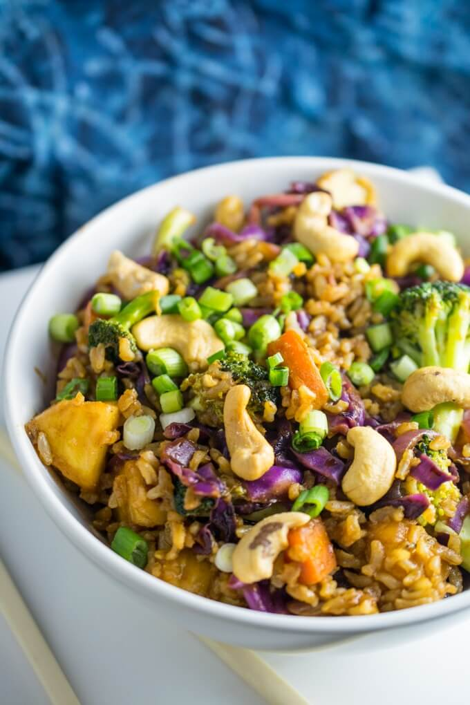 A white bowl of vegan thai pineapple fried rice with from scratch stir fry sauce with five spice powder, curry powder, and sriracha served over fresh vegetables and cashew nuts