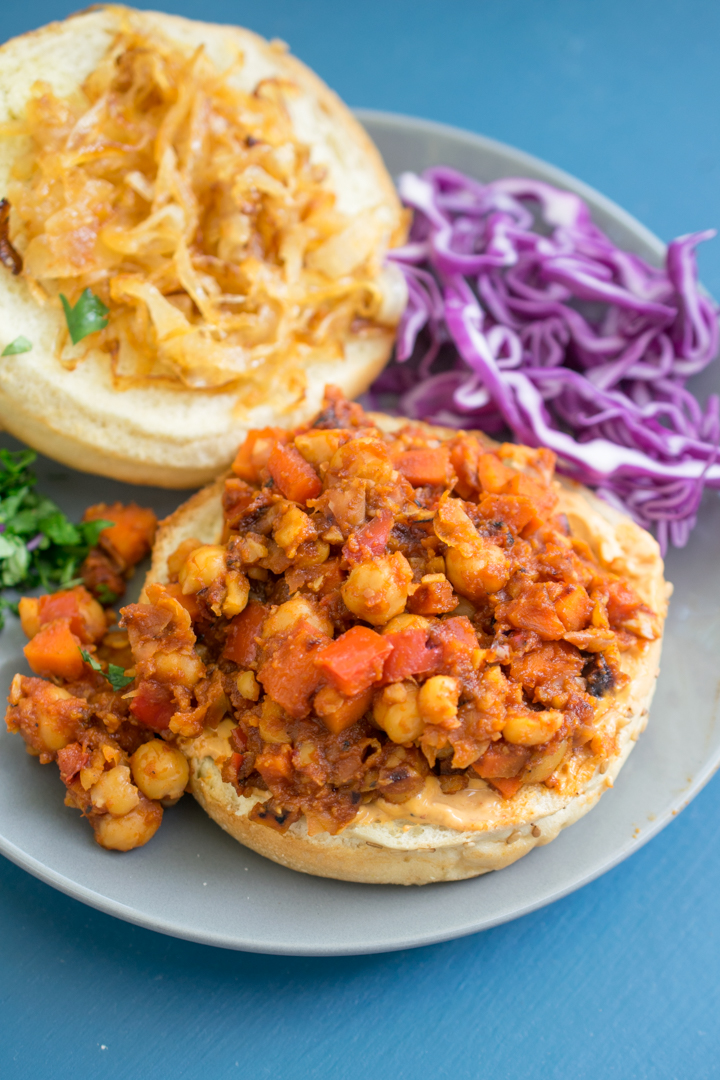 Vegan sloppy joe filling open faced on a burger bun with cabbage and onions on the plate next to it