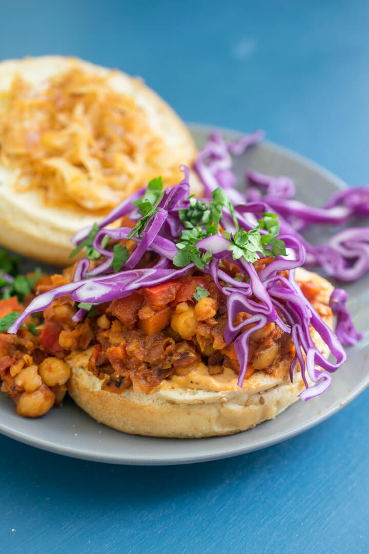 A vegan sloppy joe sandwich assembled on a bun topped with cabbage, cilantro, caramelized onions, and chipotle mayo.