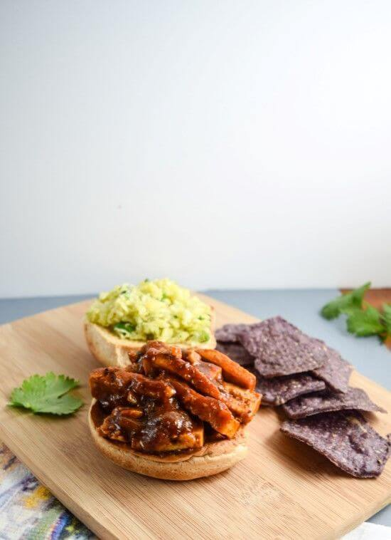Smoky, sticky, and sweet bbq sauce smothered tofu with cabbage seasoned with rice vinegar, mustard, and black pepper, garnished with cilantro and served on a whole wheat roll