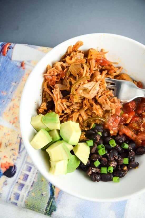 Closeup of smoky and spicy jack fruit carnitas with a homemade spice blend, served with chunky salsa, rich avocado, and black beans, topped with scallions