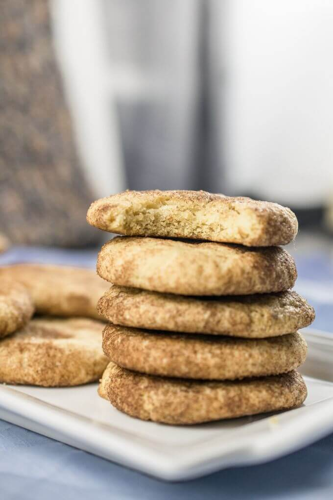 A stack of vegan snickerdoodles with a patterned curtain in the background, and a bite taken from the cookie at the top of the stack