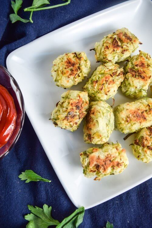 A white plate of crunchy, healthy baked brussels sprouts tater tots - make a great meal or snack, satisfy cravings, and filled with nutrient dense vegetables!