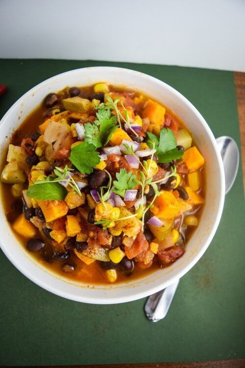 Nut, soy, and sugar free sweet potato tortilla soup - a warming blend of corn, red onions, zucchini, bell pepper, and jalapeno paired with winter sweet potatoes, garnished with cilantro and tortilla chips