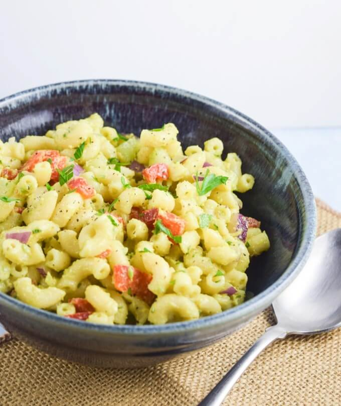 Closeup of healthy and light avocado dressed macaroni salad with crunchy red bell pepper and spicy red onion, garnished with black pepper and parsley in a blue bowl